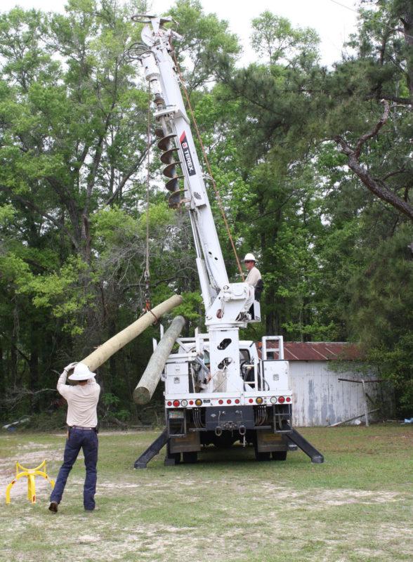 Linemen using bucket truck to left large poles.
